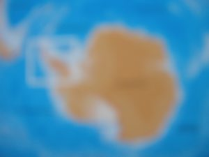 ANTICIPATION A blurred photograph of a map of Antarctica